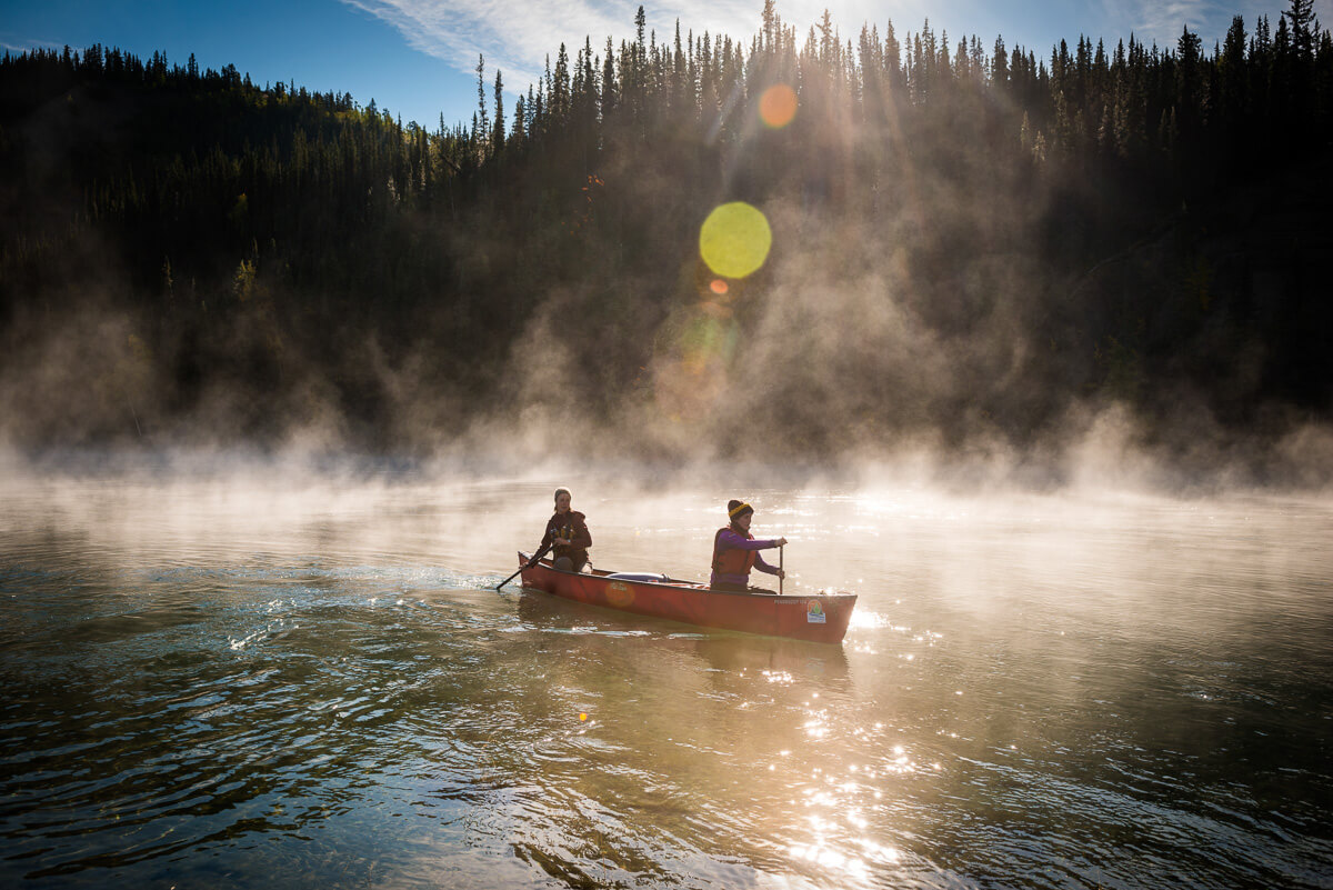 Yukon Territory, Canada, September 2014. Paddling in the early morning sun through autumn fog on the steaming Yukon river. During this Yukon River canoe trip we paddled part of the Klondike Gold Rush route of 1898. We camped on the banks of the Yukon River in authentic northern wilderness and explored the gold rush relics on the way. Photo by Frits Meyst / MeystPhoto.com